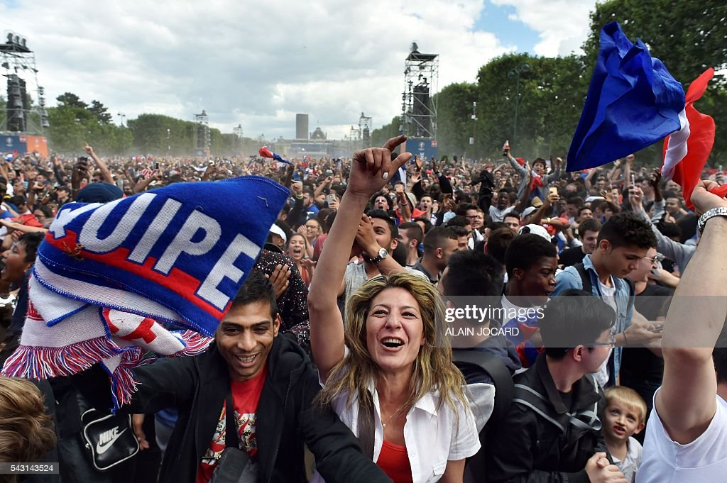 France supporters cheer as they watch the Euro 2016 tournament round of 16 football match between France and Republic of Ireland on June 26, 2016 at the Champ-de-Mars fanzone in Paris. / AFP / ALAIN