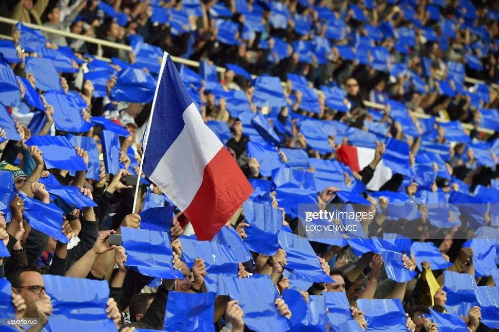 France supporters wave French flags prior to the friendly football match between France and Cameroon, at the Beaujoire Stadium in Nantes, western France, on May 30, 2016. / AFP / LOIC