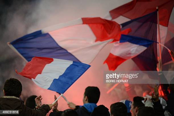 France supporters wave the national flag on November 18 2014 during an international friendly football match France vs Sweden at the Velodrome...