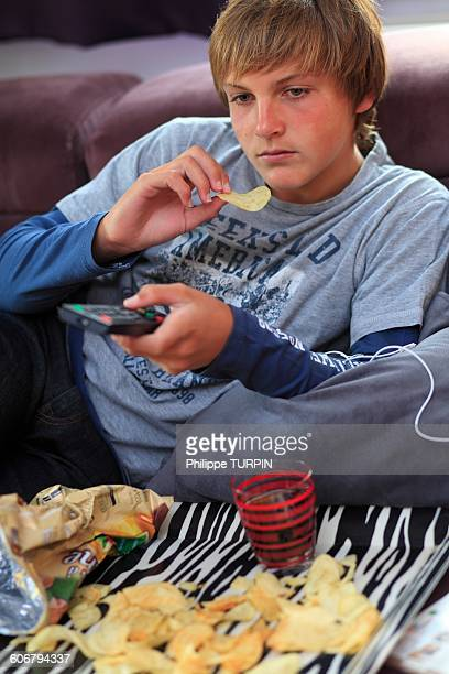 France teenager eating and watching TV