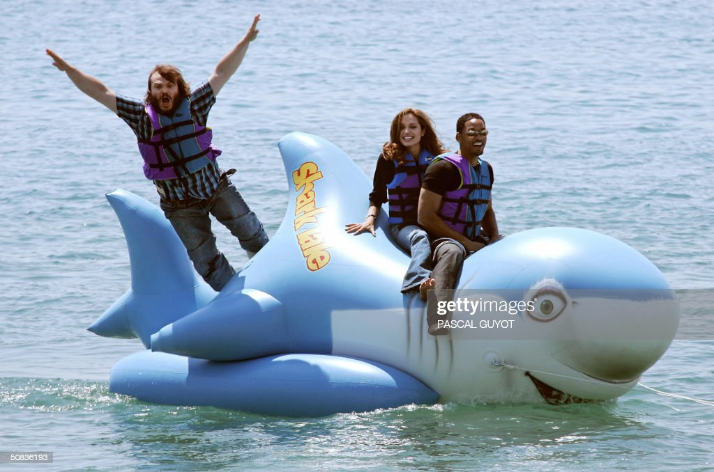 US actor Jack Black jumps into the sea as actress Angelina Jolie and Will Smith ride into shore at the Carlton Hotel beach on a promo float for their...