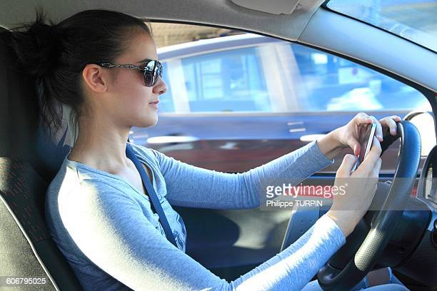 France, woman driving and using smartphone