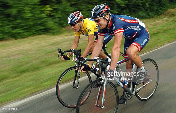 Yellow jersey US Lance Armstrong talks with his teammate US Floyd Landis during the 18th stage of the 91st Tour de France cycling race between...