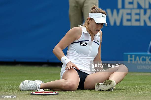 France's Alize Cornet sits on the grass after slipping against Germany's Angelique Kerber during their women's singles 2nd round match on the fifth...