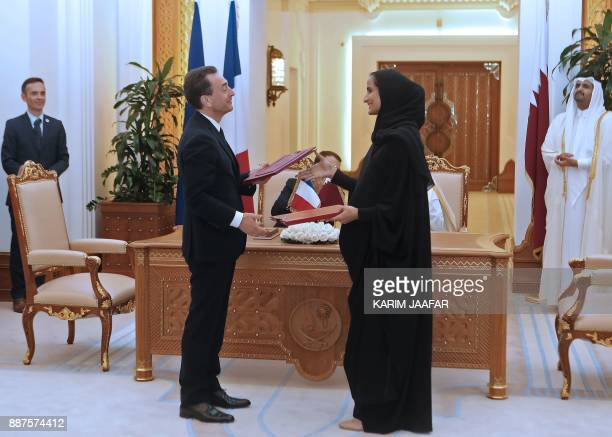 France's ambassador to Qatar Eric Chevallier exchanges a bilateral agreement with Sheikha Hind bint Hamad alThani the president of Qatar Foundation...