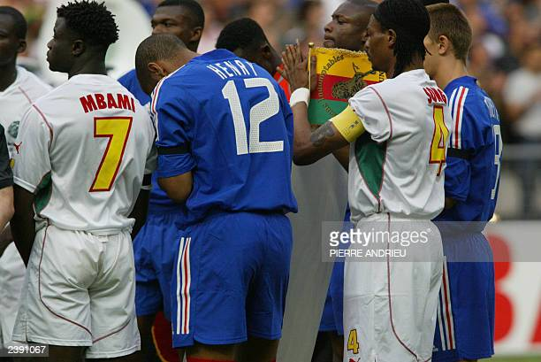 France's and cameroon's soccer players observe a minut of silence in honor of Cameroonian mildfielder MarcVivien Foe who died 26 June 2003 during the...
