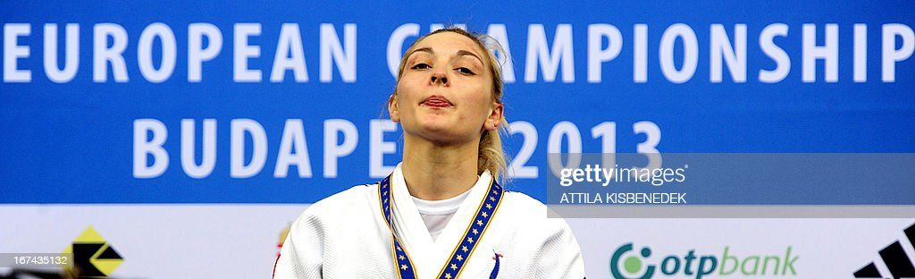 France's Automne Pavia listens to their natianal anthem on the podium after her victory over Austria's Sabrina Filzmoser (not pictured) after their final of the Judo European Championships in 57kg category for women in Budapest. Pavia won the gold medal. AFP PHOTO / ATTILA KISBENEDEK
