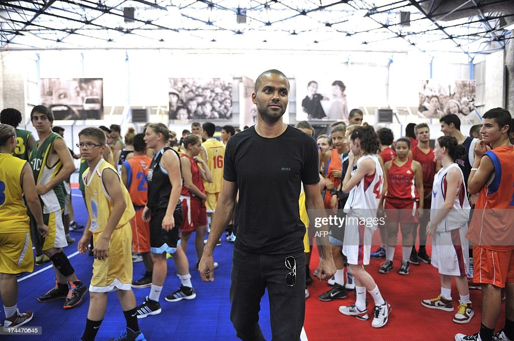 France's basketball and US San Antonio Spurs' team player Tony Parker (C) arrives to take part in a training session with teenagers during the 'Tony Parker Camp' on July 26, 2013 in Villeurbanne, near Lyon, southeastern France.