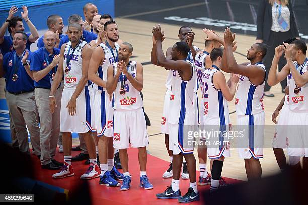 France's basketball point guard Tony Parker and his teammates celebrate with their Bronze medal after France defeated Serbia to place third at the...