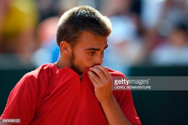 France's Benjamin Bonzi reacts after a point against Spain's Albert RamosVinolas during their tennis match at the Roland Garros 2017 French Open on...