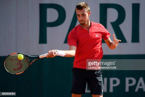 France's Benjamin Bonzi returns the ball to Spain's Albert RamosVinolas during their tennis match at the Roland Garros 2017 French Open on May 31...