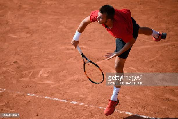 France's Benjamin Bonzi serves to Spain's Albert RamosVinolas during their tennis match at the Roland Garros 2017 French Open on May 31 2017 in Paris...