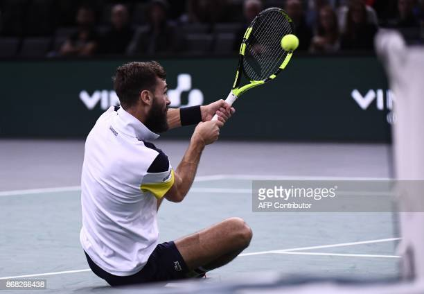 France's Benoit Paire returns the ball as he falls during his first round match against France's Richard Gasquet at the Paris Masters ATP tennis Open...