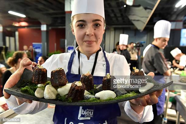 France's Best Apprentice 2016 and professional canele pastry world champion 2016 Alissia Morandeau poses with caneles a small French pastry flavored...