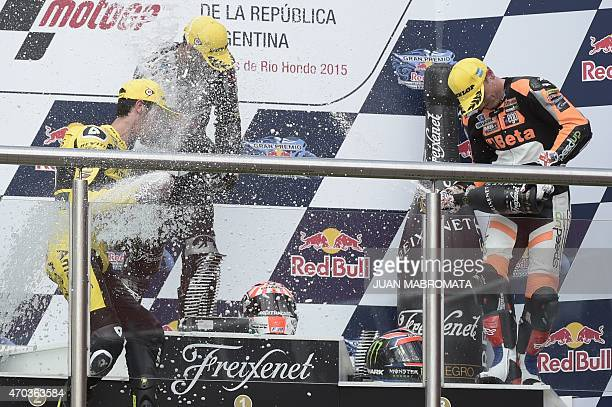 France's biker Johann Zarco Spain's Alex Rins and Great Britain's Sam Lowes spray champagne at the podium of the Moto2 race of the Argentina Grand...