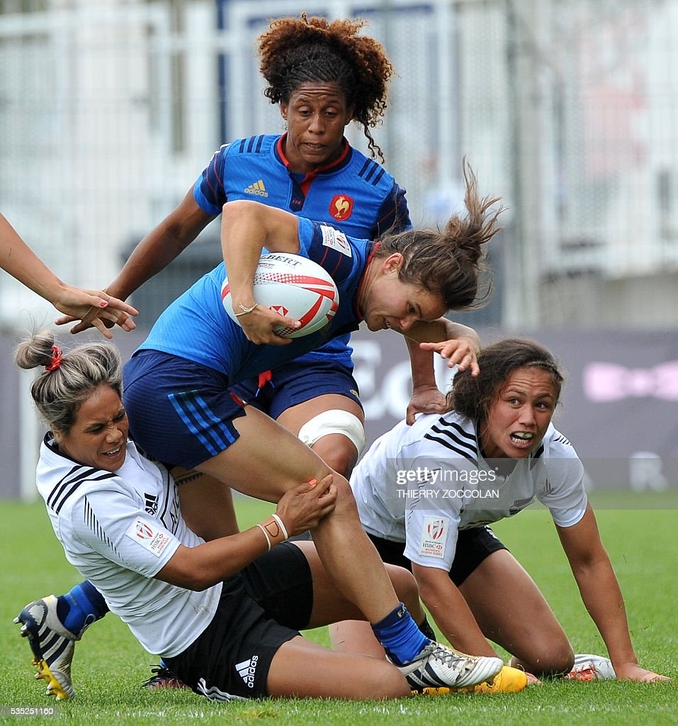 France's Camille Grassineau (C) is tackled by New Zealand's players during the HSBC World Rugby Women's Sevens Series match between New Zealand and France on May 29, 2016 at the Gabriel Montpied stadium in Clermont-Ferrand, central France.