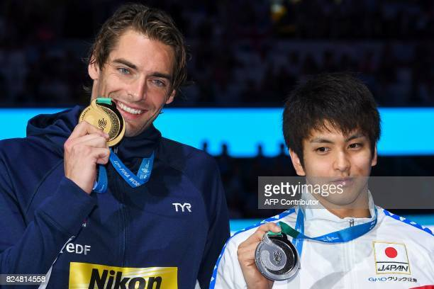 France's Camille Lacourt and Japan's Junya Koga poses with their gold medal on the podium of the men's 50m backstroke during the swimming competition...
