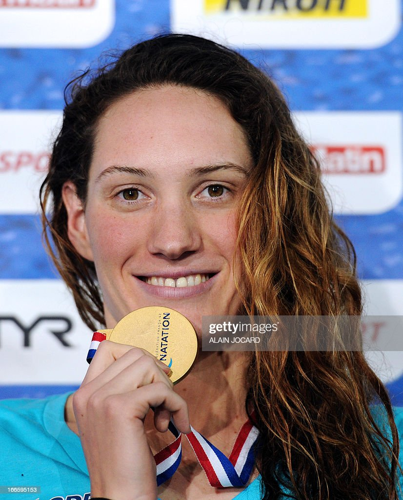 France's Camille Muffat smiles on the podium after winning the women's 200m freestyle final of the French swimming championships on April 14, 2013, in Rennes, western France.