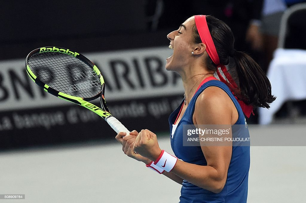 France's Caroline Garcia celebrates after winning her Fed Cup World Group first round tennis match against Italy's Camila Giorgi in Marseille, southern France, on February 7, 2016. / AFP / ANNE-CHRISTINE POUJOULAT