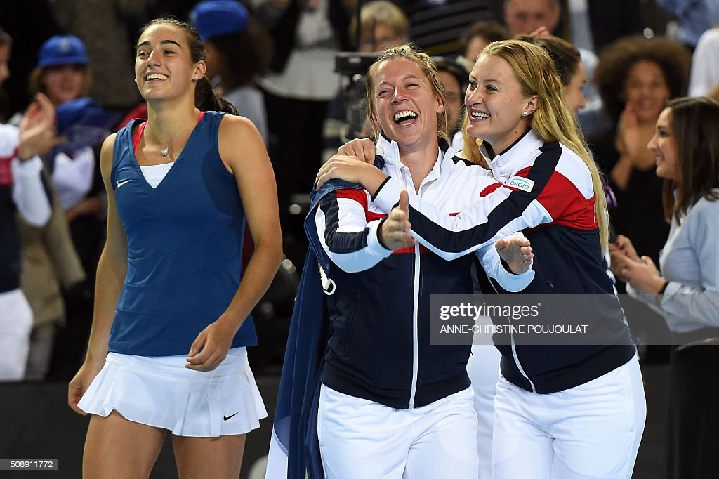 France's Caroline Garcia, Pauline Parmentier and Kristina Mladenovic celebrate after winning the Fed Cup World Group first round tennis match against Italy in Marseille, southern France, on February 7, 2016. / AFP / ANNE-CHRISTINE POUJOULAT