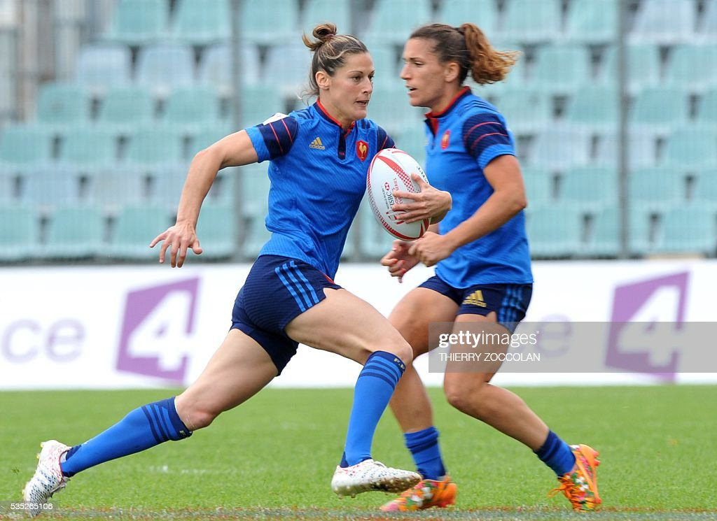 France's Caroline Ladagnous (L) runs with the ball next to France's Fanny Horta (R) during the HSBC World Rugby Women's Sevens Series match between New Zealand and France on May 29, 2016 at the Gabriel Montpied stadium in Clermont-Ferrand, central France.