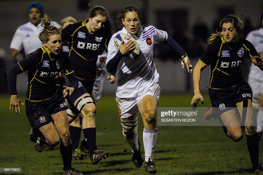 France's center Lucille Godiveau (C) runs with the ball during the Six Nations women's international rugby union match between France and Scotland at the Bourillot Stadium in Longvic, eastern France, on March 15, 2013.