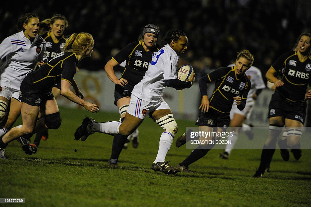 France's center Sandrine Agricole (C) runs with the ball during the Six Nations women's international rugby union match between France and Scotland at the Bourillot Stadium in Longvic, eastern France, on March 15, 2013. AFP PHOTO / SEBASTIEN BOZON