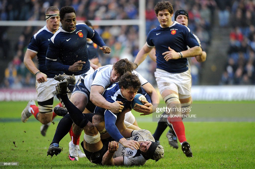 France's center Yannick Jauzion vies with Scotland's flanker Kelly Brown and hooker Ross Ford as France's Imanol Harinordoquy Fulgence Ouedraogo and...