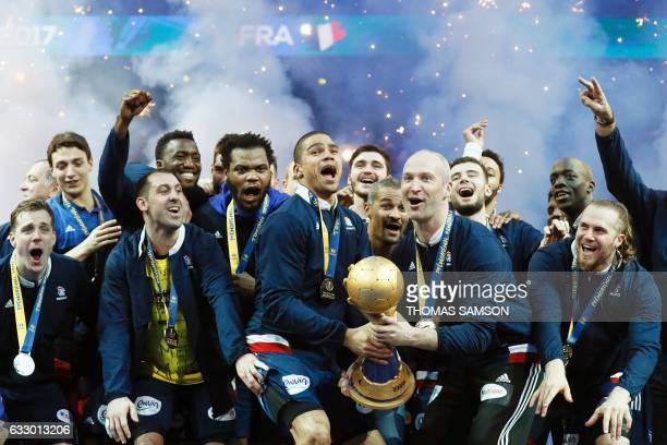 France's centre back Daniel Narcisse and France's goalkeeper Thierry Omeyer hold thwe winner's trophy as France's teammates and staff celebrate...