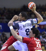 France's centre back Daniel Narcisse jumps to score between Serbia's pivot Alem Toskic and right back Nemanja Zelenovic during the men's EHF Euro...