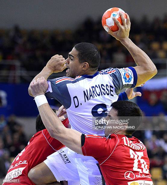 France's centre back Daniel Narcisse jumps to score between Serbia's pivot Alem Toskic and right back Nemanja Zelenovic during the men's EHF Euro...