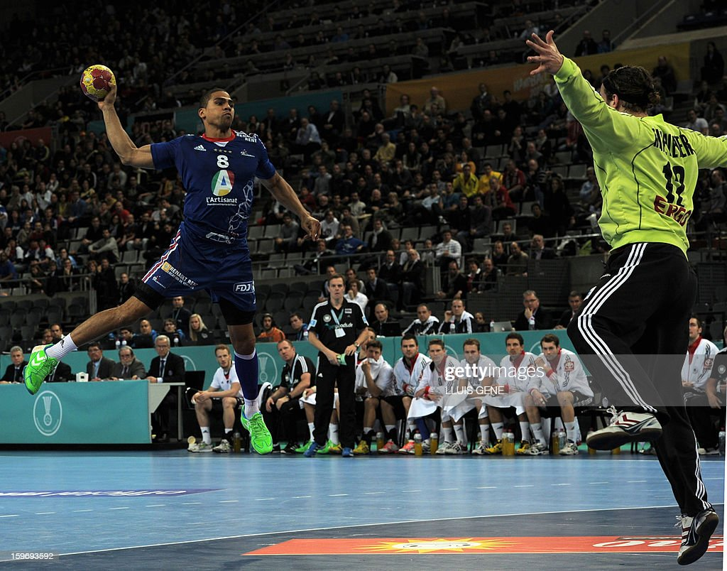 France's centre back Daniel Narcisse (L) shoots a ball against Germany's goalkeeper Silvio Heinevetter (R) during the 23rd Men's Handball World Championships preliminary round Group A match France vs Germany at the Palau Sant Jordi in Barcelona on January 18, 2013.