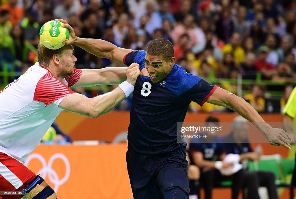 TOPSHOT France's centre back Daniel Narcisse tries to get past Denmark's pivot Rene Toft Hansen during the men's Gold Medal handball match Denmark vs...