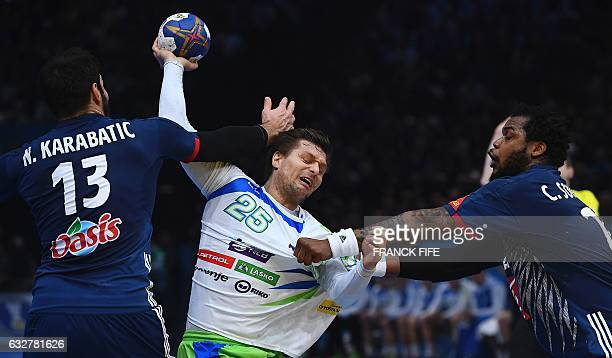 TOPSHOT France's centre back Nikola Karabatic and France's pivot Cedric Sorhaindo hold back Slovenia's centre back Marko Bezjak during the 25th IHF...