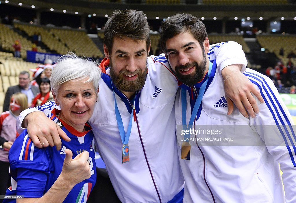 France's centre back Nikola Karabatic (R) and his brother pivot Luka Karabatic celebrate with their mother Lala (L) after the podium ceremony of the men's EHF Euro 2014 Handball Championship on January 26, 2014 at the Boxen Arena in Herning, Denmark. France won the tournament ahead of Denmark and Spain.