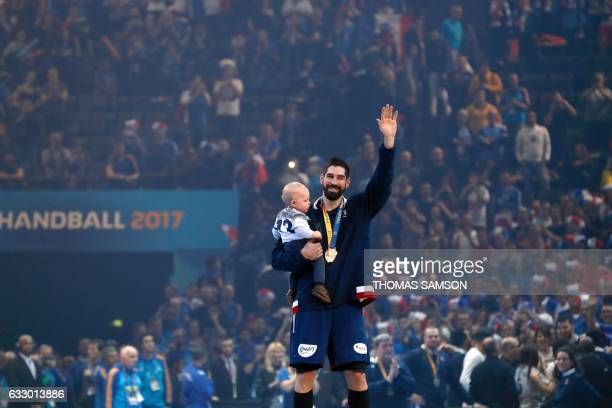 TOPSHOT France's centre back Nikola Karabatic holds his son Alek as he celebrates after the podium ceremony following France's win during the 25th...