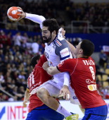 France's centre back Nikola Karabatic jumps to score on Serbia's right back Marko Vujin and pivot Alem Toskic during the men's EHF Euro 2014 Handball...