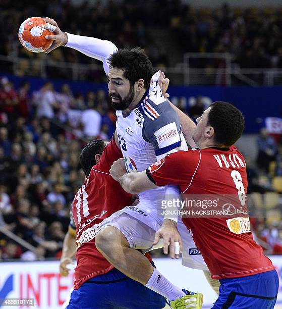France's centre back Nikola Karabatic jumps to score on Serbia's right back Marko Vujin and pivot Alem Toskic during the men's EHF Euro 2014 Handball...