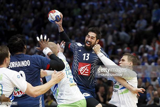 TOPSHOT France's centre back Nikola Karabatic passes the ball under pressure from Slovenia's pivot Vid Poteko during the 25th IHF Men's World...