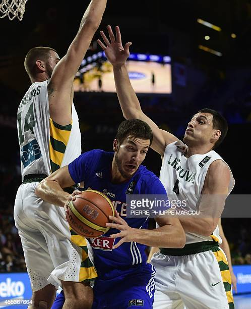 France's centre Joffrey Lauvergne vies with Lithuania's centre Jonas Valanciunas and Lithuania's forward Jonas Maciulis during the 2014 FIBA World...