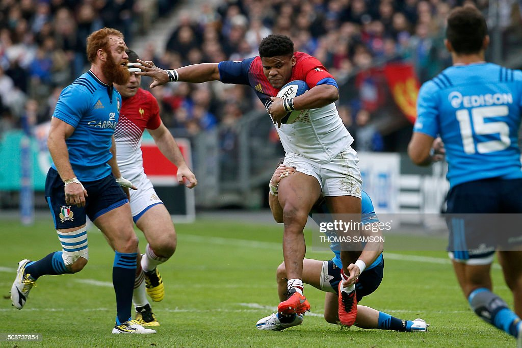 France's centre Jonathan Danty (C) runs to evade Italy's centre Gonzalo Garcia (L) during the Six Nations international rugby union match between France and Italy at the Stade de France in Saint-Denis, north of Paris, on February 6, 2016. AFP PHOTO / THOMAS SAMSON / AFP / THOMAS SAMSON