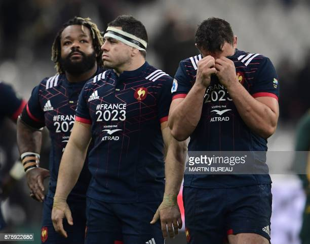 France's centre Mathieu Bastareaud < France's hooker Guilhem Guirado and France's number eight Louis Picamoles react after defeat in the friendly...