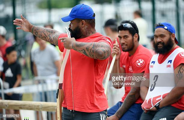 France's centre Mathieu Bastareaud gestures to aim at a target in front of France's lock Sebastien Vahaamahina and prop Uini Atonio during an archery...