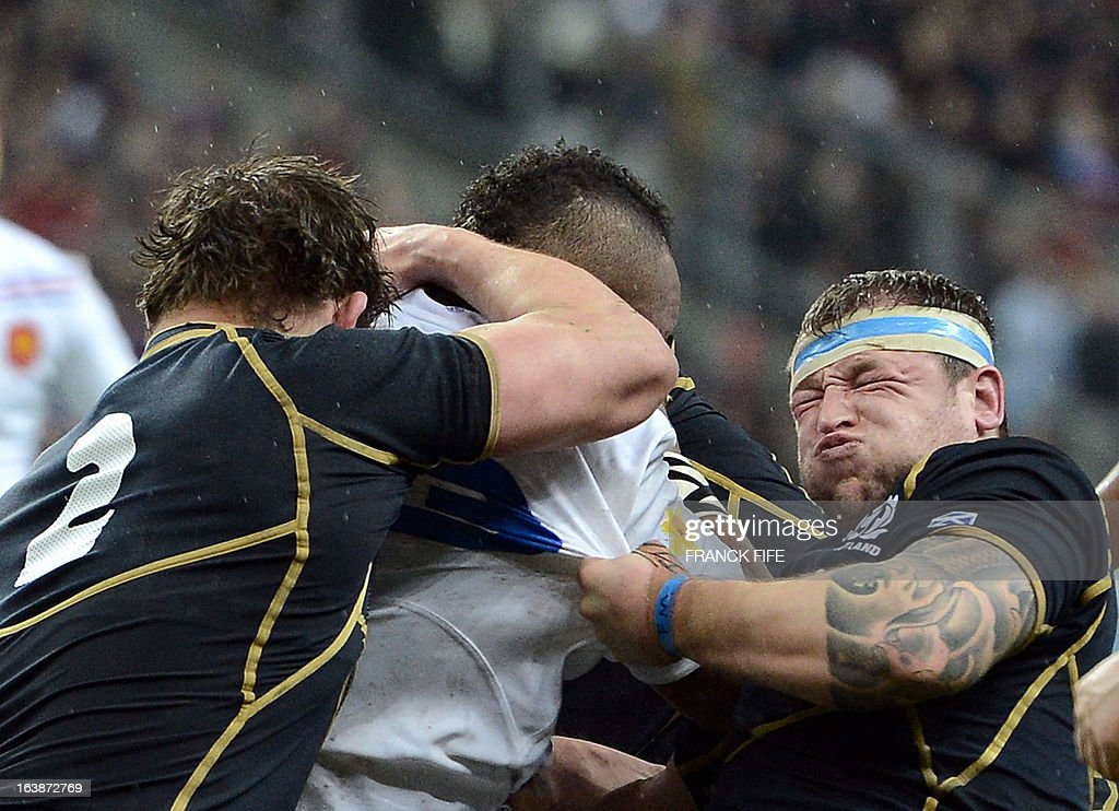 France's centre Mathieu Bastareaud (C) is tackled by Scotland's loose head prop Ryan Grant (R) and Scotland's hooker Ross Ford during the Six Nations International Rugby Union match between France and Scotland at the Stade de France, in Saint-Denis, near Paris on March 16, 2013. France won 23-16 and finished last in the tournament. AFP PHOTO / FRANCK FIFE