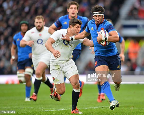 France's centre Maxime Mermoz hands off England's scrum half Ben Youngs during the Six Nations international rugby union match between England and...