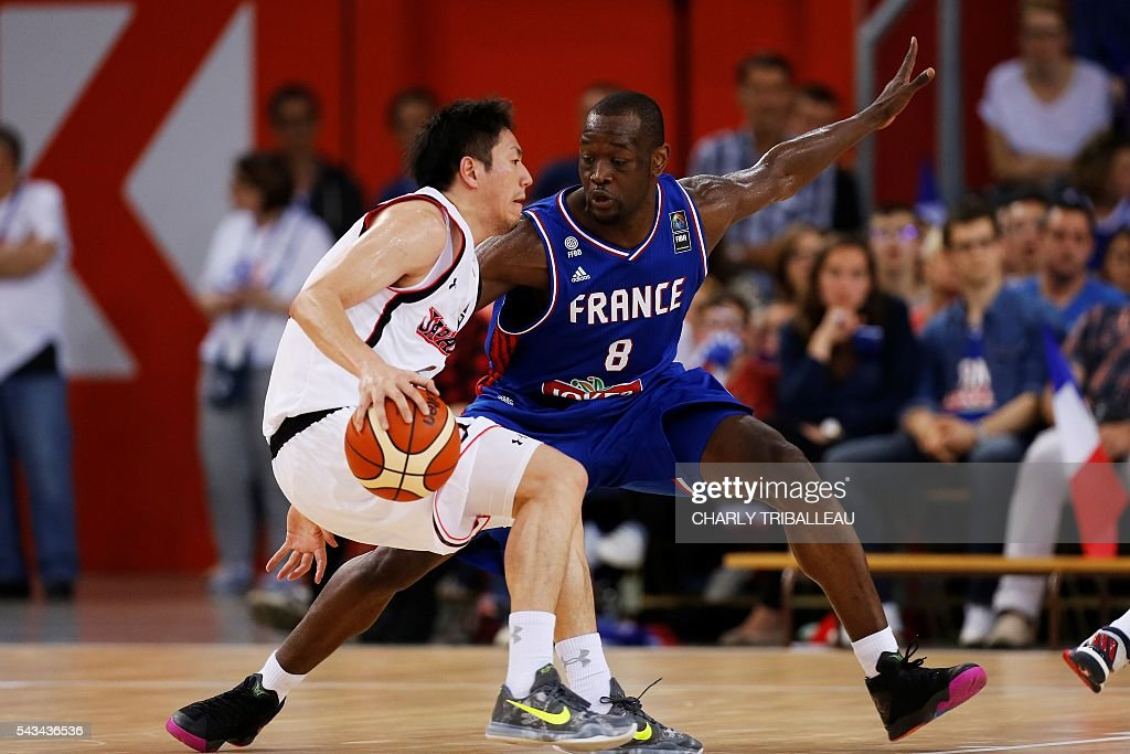 France's Charles Kahudi (R) vies with Japan's Makoto Hiejima (L) during the basketball match between France and Japan at the Kindarena hall in Rouen on June 28, 2016. / AFP / CHARLY