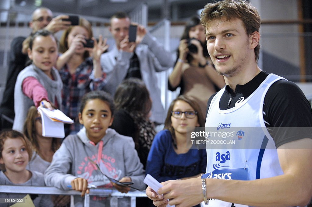 france's Christophe Lemaitre (R) signs autographs after finishing third in the men's 60m race at the 2013 French Indoor Athletics championships on February 16, 2013 in Aubiere, central France. ZOCCOLAN