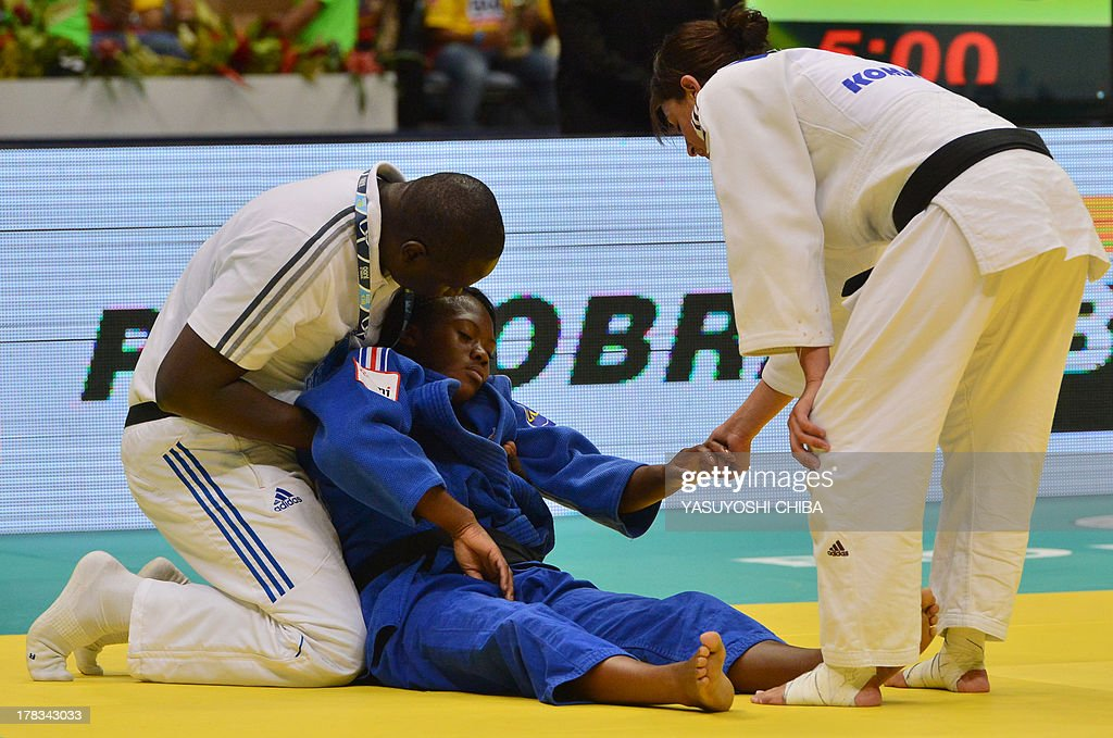 France's Clarisse Agbegnenou (C) is assisted during the women's -63kg category final against Israel's Yarden Gerbi (out of frame), during the IJF World Judo Championship, in Rio de Janeiro, Brazil, on August 29, 2013. AFP PHOTO / YASUYOSHI CHIBA