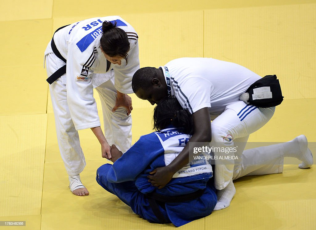 France's Clarisse Agbegnenou(blue) is helped by a paramedic next to her competitor Israel's Yarden Gerbi(white) competes with in the women's 63kg category final of the IJF World Judo Championship in Rio de Janeiro, Brazil, on August 29, 2013. AFP PHOTO / VANDERLEI ALMEIDA