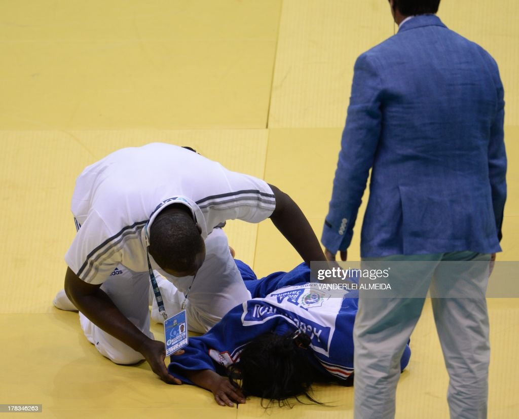 France's Clarisse Agbegnenou(blue) lies on the floor helped by a paramedic after the fight against Israel's Yarden Gerbi after the women's 63kg category final of the IJF World Judo Championship in Rio de Janeiro, Brazil, on August 29, 2013.